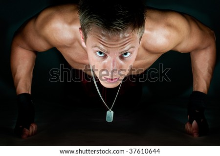Muscular male kick-boxer doing push-up on his knuckles