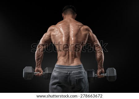 Muscular male model bodybuilder doing exercises with dumbbells, turned back. Isolated over black background. - stock photo