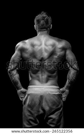 Muscular male model bodybuilder preparing for fitness training, turned back - stock photo