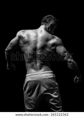 Muscular male model bodybuilder preparing for fitness training, turned back - stock photo