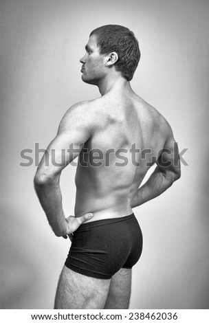 Muscular male model posing. Back view. Black and white.