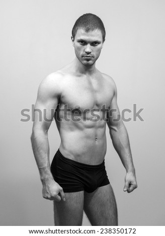 Muscular male model posing. Black and white. - stock photo
