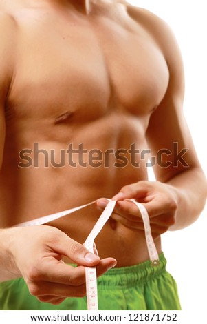 Muscular male torso is being measured isolated on white - stock photo