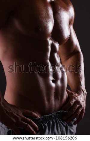 Muscular male torso isolated on black - stock photo