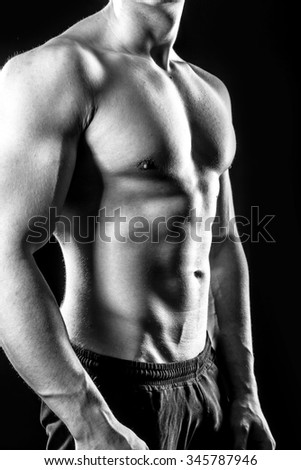 Muscular male torso isolated on black, black and white photography