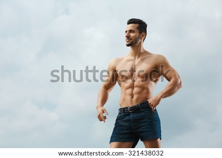 Muscular male torso on a background sky. Athletic and muscular man with naked torso posing on the sky background, looking away - stock photo
