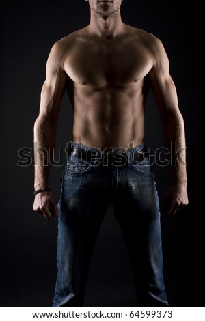 Muscular male torso on a black background - stock photo
