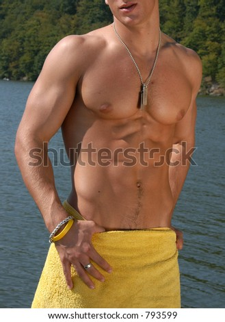Muscular male torso with army tags wrapped a towel - stock photo