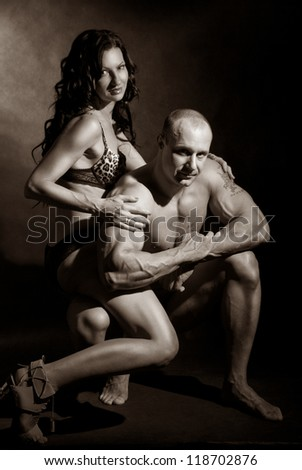 Muscular man and a woman posing in studio on dark background.toning - stock photo