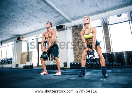 Muscular man and fit woman lifting kettle ball at gym - stock photo