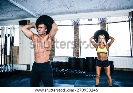 Muscular man and fit woman workout at crossfit gym - stock photo