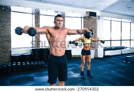 Muscular man and sporty woman lifting dumbbells at gym - stock photo