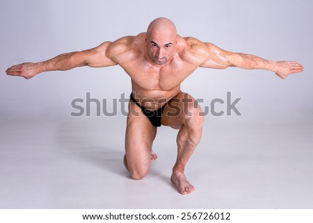 Muscular man bodybuilder is demonstrating his perfect muscular body  muscles and arms. Isolated over gray background. - stock photo