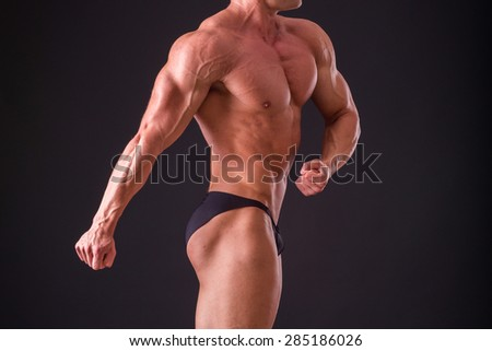 Muscular man bodybuilder. Man posing on a black background, shows his muscles. Bodybuilding, posing, black background, muscles. - stock photo