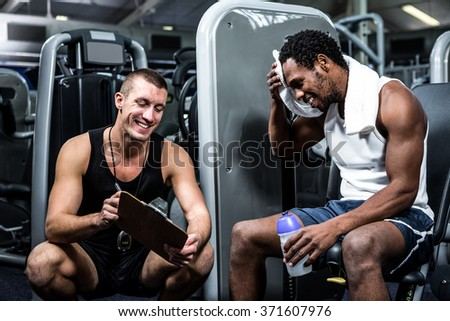 Muscular man discussing performance with trainer at gym - stock photo
