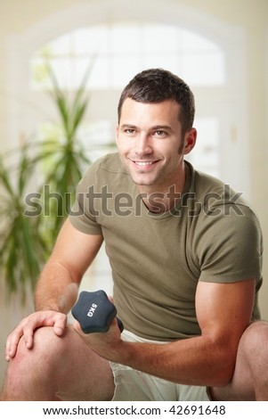 Muscular man doing biceps exercise at home with hand barbell, smiling. - stock photo