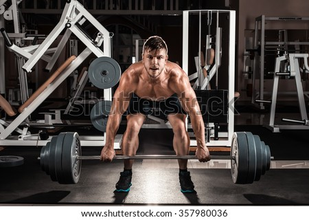 Muscular Man Doing Heavy Deadlift Exercise. Young athlete getting ready for weight lifting training - stock photo