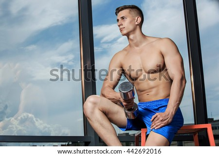 Muscular man doing heavy weight exercise for biceps with dumbbells