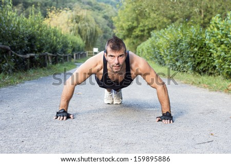 Muscular man doing push up in the park. - stock photo