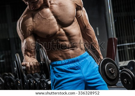 Muscular man during workout in the gym - stock photo