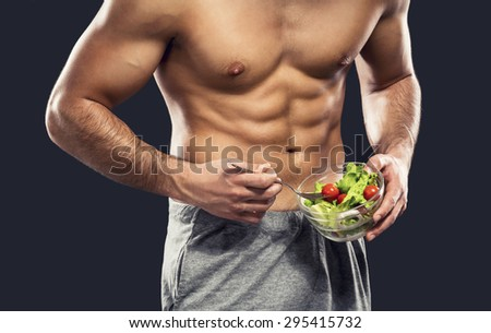 Muscular man eating a healthy salad, isolated over a gray background - stock photo