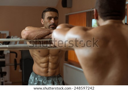 Muscular Man Flexing Abdominal Muscles Abs In A Health Club - stock photo
