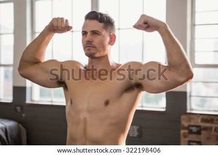 Muscular man flexing muscles at the gym - stock photo