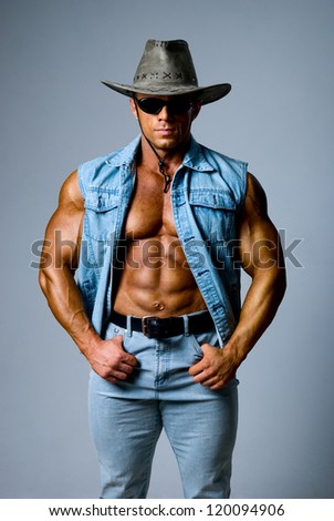 Muscular man in a cowboy hat on a gray background