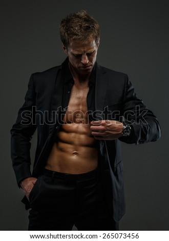 Muscular man in a suit posing in studio isolated on grey - stock photo