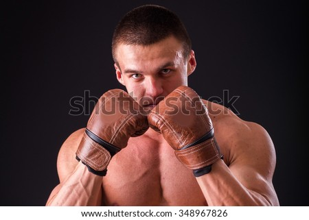 Muscular man in boxing gloves on a dark background. Professional boxer boxing shows muscle in racks. Beautiful muscular body boxer. Photos for sporting magazines, posters and websites. - stock photo