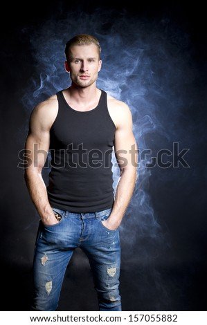 Muscular man in smoke - stock photo