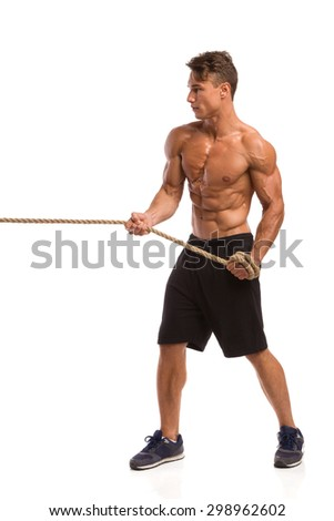Muscular man in sport shorts and sneakers pulling a rope. Full length studio shot isolated on white. - stock photo