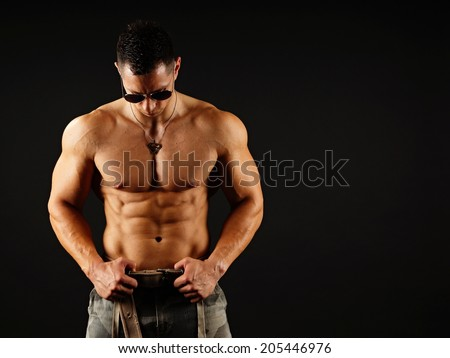 Muscular man in sunglasses on dark background, right you can write some text  - stock photo