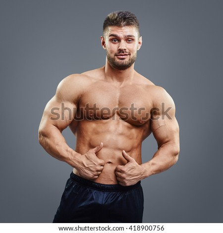 Muscular man is looking at the camera and showing thumbs up sign on grey background. Fitness trainer showing thumbs up gesture. - stock photo
