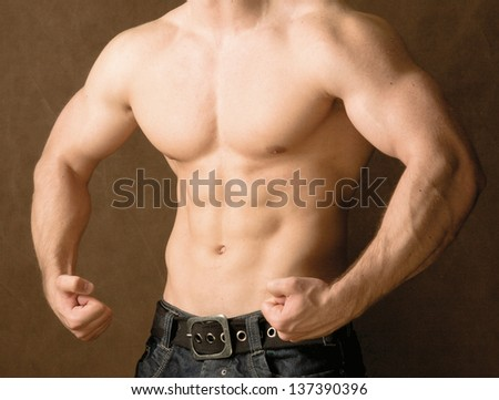 Muscular man, isolated on brown background - stock photo