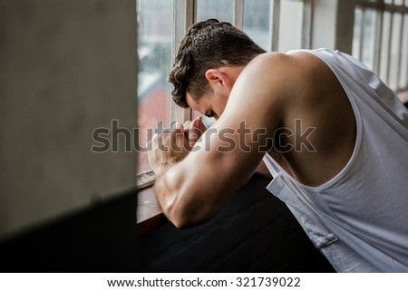 Muscular man leaning on window at the gym