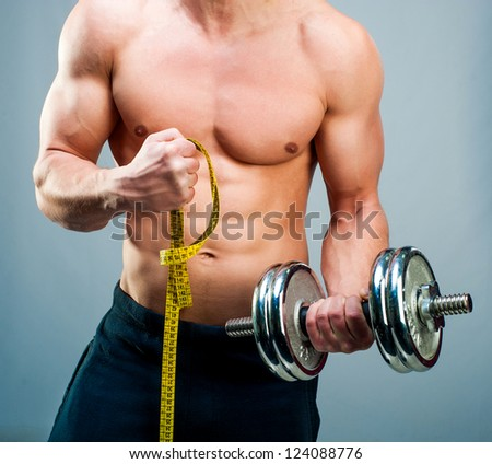 muscular man measuring his biceps with dumbbells - stock photo
