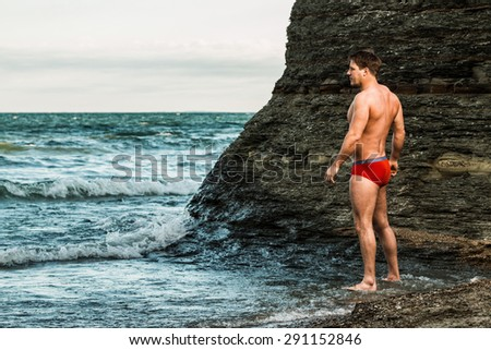 Muscular man on a beach in underwear. - stock photo