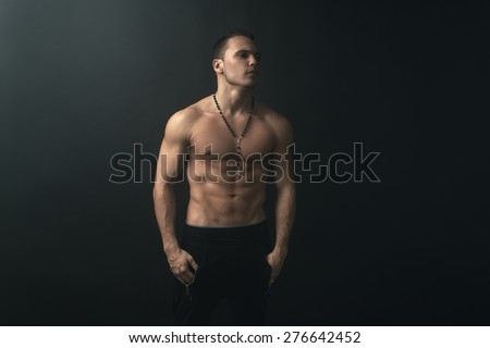 muscular man on a dark background - stock photo
