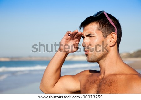 Muscular man overlooking the ocean using his hand as a shade. - stock photo