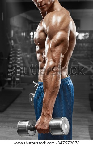 Muscular man posing in gym, showing triceps. Strong male naked torso abs, working out, focus on the hand - stock photo