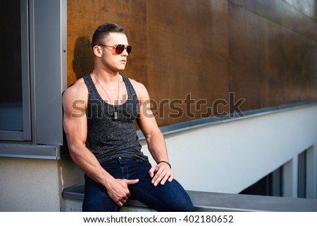 Muscular man posing near building - stock photo