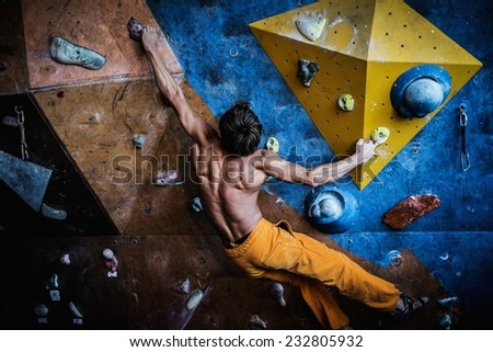 Muscular man practicing rock-climbing on a rock wall indoors  - stock photo