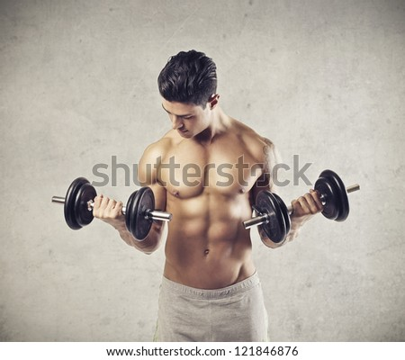 Muscular man raising two dumbbells - stock photo