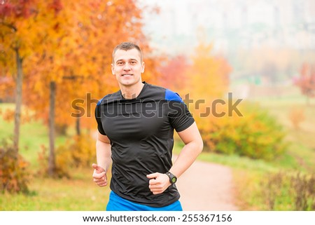 muscular man running on a footpath in the park - stock photo
