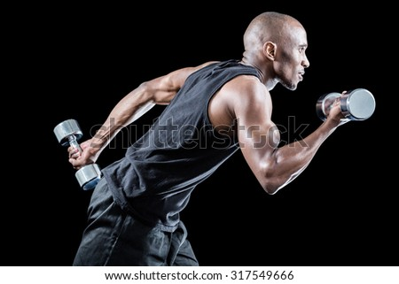 Muscular man running while holding dumbbell against black background - stock photo
