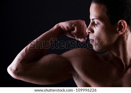 Muscular man showing his strong biceps over white background - stock photo