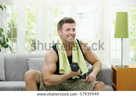 Muscular man sitting on sofa at home, doing excercise with hand barbell. - stock photo