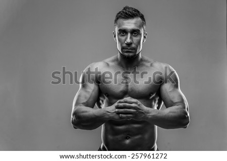 Muscular man standing over gray background. HDR monochrome. - stock photo
