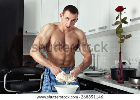 Muscular man stands in the kitchen and knead the dough. He wears an apron, arms dough. - stock photo